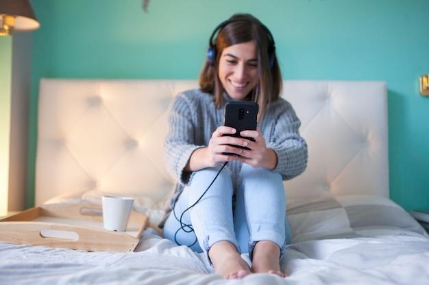 Jovem mulher usando fones de ouvido e tomando café da manhã