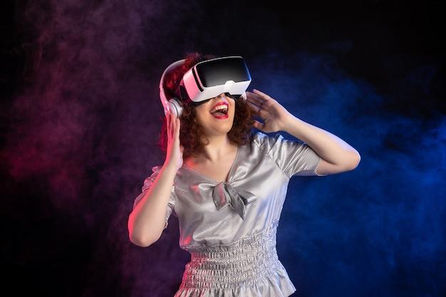 Jovem mulher usando headset vr em fones de ouvido na reprodução de vídeo de videogame escuro