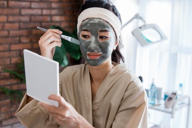 Jovem mulher usando lama de máscara facial Foto Premium