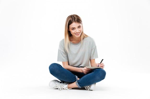 Jovem mulher usando lápis e caderno