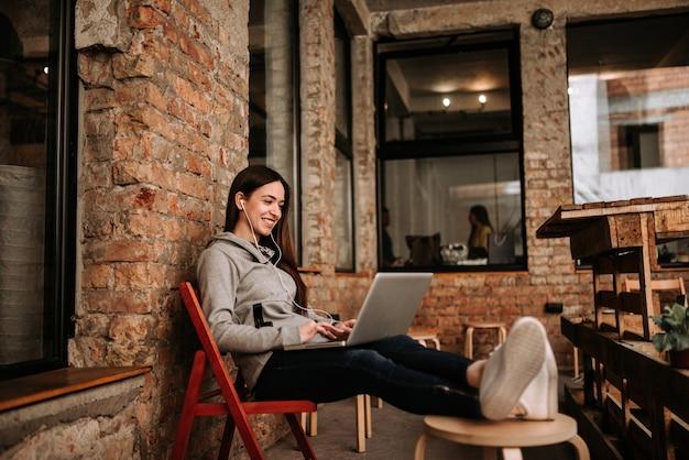 Jovem mulher usando laptop enquanto escuta música em fones de ouvido. parede de tijolos no fundo.