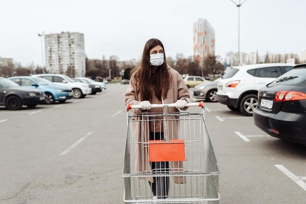 Jovem mulher usando máscara facial de proteção contra o coronavírus 2019-ncov empurrando um carrinho de compras.