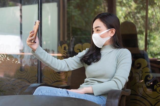 Jovem mulher usando máscara médica fazendo selfie com smartphone em um café, novo estilo de vida normal