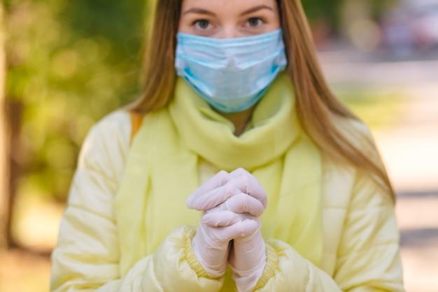 Jovem mulher usando máscara para prevenir o coronavírus e orando a deus para detê-lo na natureza
