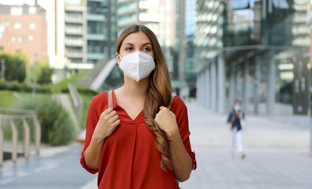 Jovem mulher usando máscara protetora kn95 ffp2, andando na rua da cidade moderna.
