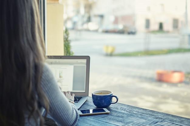 Jovem mulher usando o celular e laptop no escritório ou café. conceito de trabalho remoto