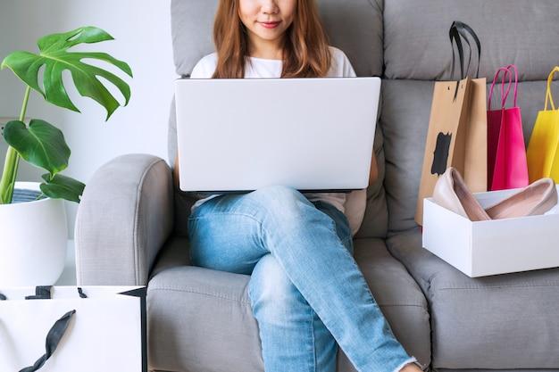 Jovem mulher usando o computador portátil, sentado no sofá com seus itens de moda de compras pacote on-line. compras on-line, internet banking, trabalhando em / em casa, novo conceito de estilo de vida normal