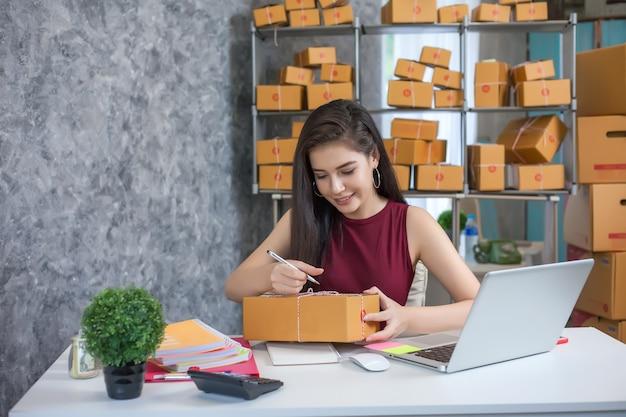 Jovem mulher usando o computador portátil. sucesso dos empresários em fazer negócios. expedição onlin