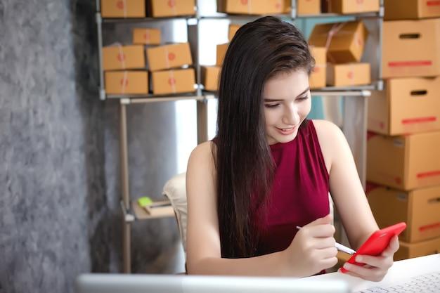 Jovem mulher usando o laptop de telefone inteligente e computador. sucesso dos empresários em fazer negócios