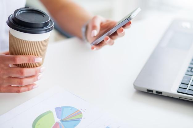 Jovem, mulher, usando o telefone dela e beber café no escritório