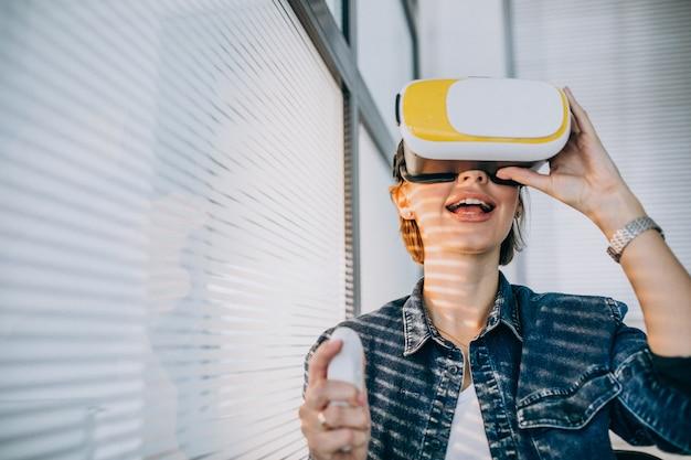 Jovem mulher usando óculos vr e jogando jogo virtual usando o controle remoto