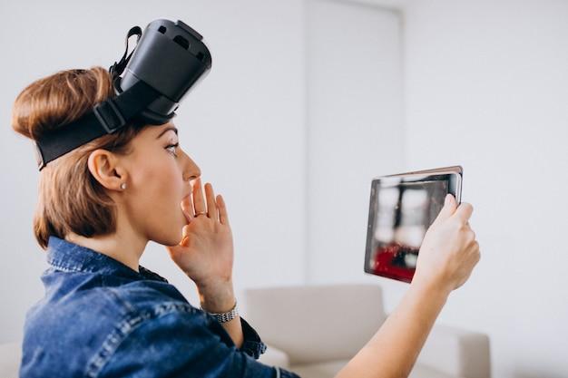 Jovem mulher usando óculos vr e usando tablet