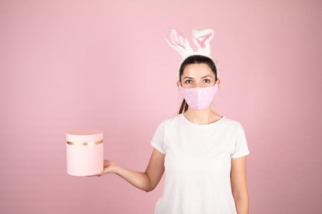 Jovem mulher usando orelhas de coelho e segurando uma caixa de presente rosa. morena em máscara protetora e camiseta branca em fundo rosa. conceito de banner de páscoa. foto de alta qualidade