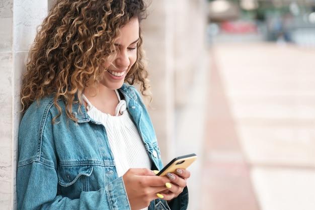 Jovem mulher usando seu telefone celular ao ar livre na rua.