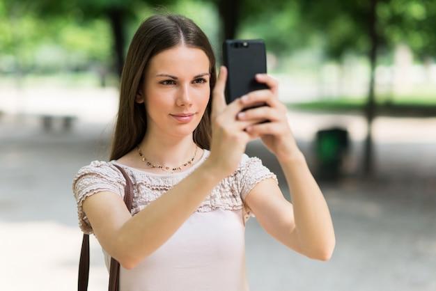 Jovem, mulher, usando seu telefone celular para tirar uma foto