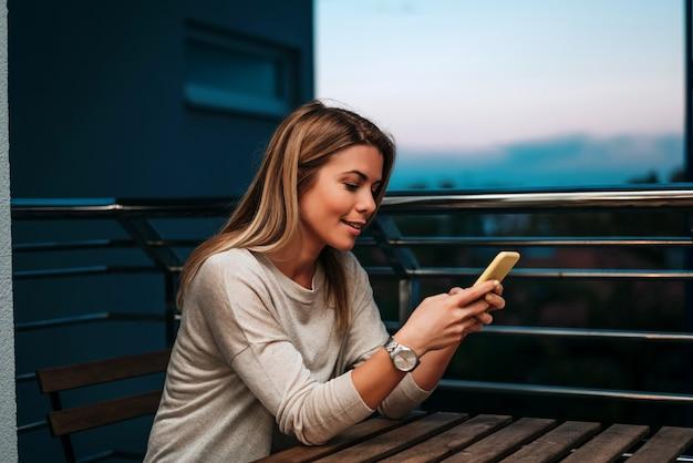 Jovem mulher usando smartphone à noite.