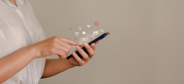 Jovem mulher usando smartphone com ícone social pop-up uma jovem mulher de negócios está usando um telefone celular para pesquisar informações e mídias sociais na internet. conceito de tecnologia e pessoas