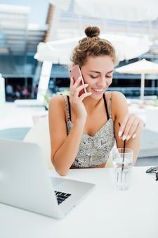 Jovem mulher usando smartphone em uma cafeteria ao ar livre.