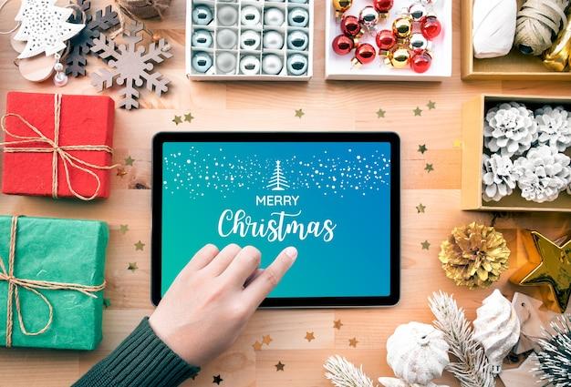 Jovem mulher usando tablet com texto de feliz natal na tela e enfeite