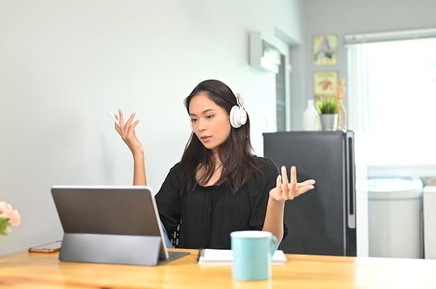Jovem mulher usando tablet para videochamada com seu colega em casa.
