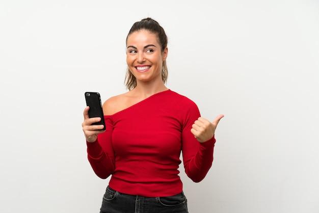 Jovem mulher usando telefone celular, apontando para o lado