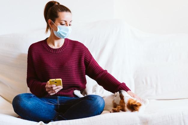 Jovem mulher usando telefone celular, cachorro pequeno bonito, além de. sentado no sofá, usando máscara protetora. fique em casa conceito durante o coronavírus covid-2019