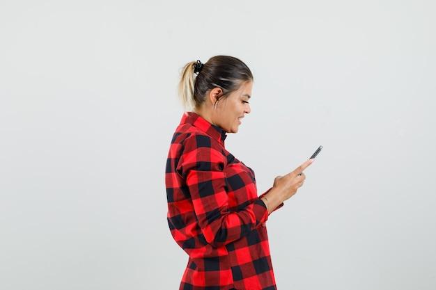 Jovem mulher usando telefone celular com camisa e parece alegre.
