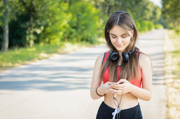 Jovem mulher usando telefone celular e fones de ouvido enquanto passeava no campo à noite