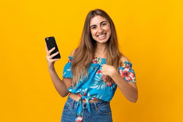 Jovem mulher usando telefone celular isolado amarelo com expressão facial de surpresa