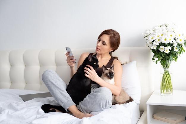 Jovem mulher usando telefone com seus dois gatos sentados juntos no quarto com flores.