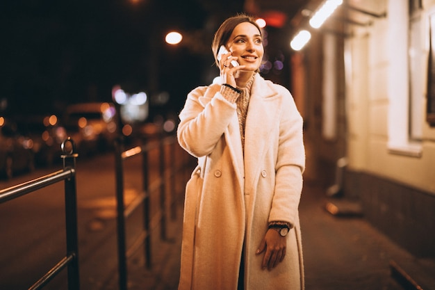 Jovem mulher usando telefone fora da rua à noite