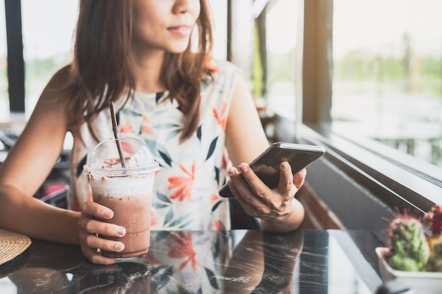 Jovem mulher usando telefone inteligente com bebidas no café