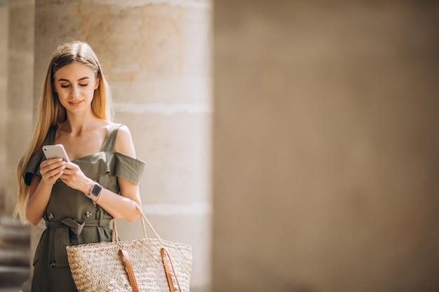 Jovem mulher usando telefone pelo prédio antigo