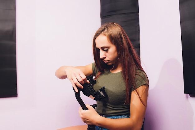 Jovem mulher usando um estabilizador de câmera de cardan para gravar imagens dentro de uma casa. filmando antiguidades diferentes usando uma câmera profissional e moderna de espelhos.