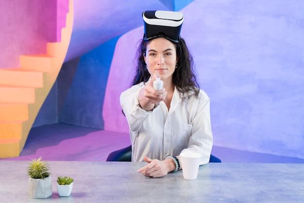 Jovem mulher usando um fone de ouvido da realidade virtual e controle remoto