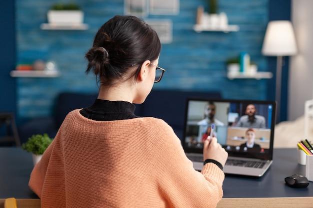Jovem mulher usando um laptop, falando com o colega sobre o projeto de comunicação da escola durante a reunião de videochamada da universidade. aluno em educação de e-learning remoto durante quarentena de coronavírus