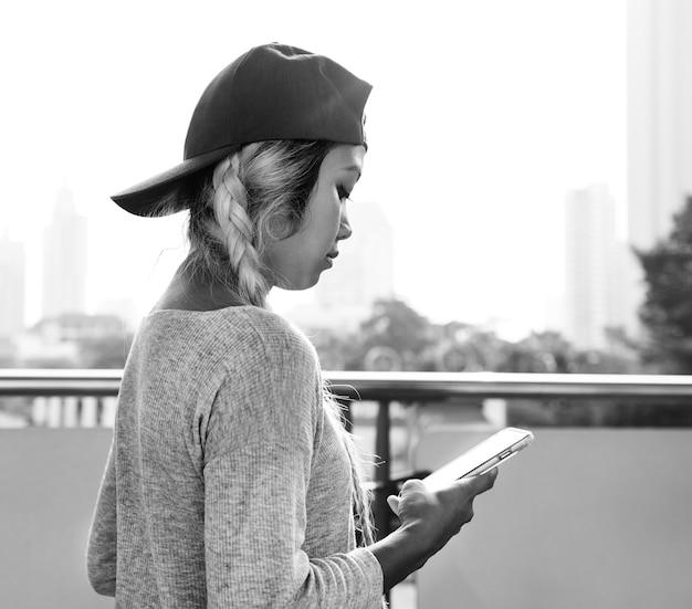 Jovem mulher usando um smartphone na paisagem urbana