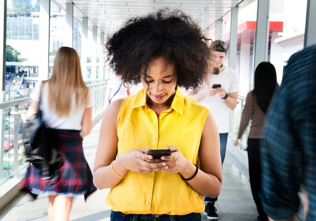 Jovem, mulher, usando um smartphone no meio da multidão andando