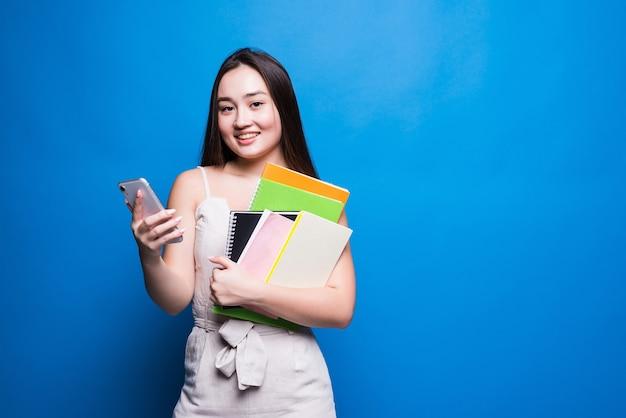 Jovem mulher usando um telefone celular enquanto segura livros didáticos em pé, isolados na parede azul,