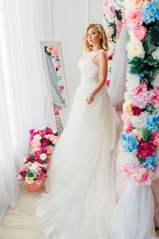 Jovem mulher usando vestido de noiva posando no quarto decorado com flores