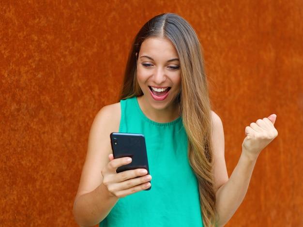 Jovem mulher vencedora parece seu telefone inteligente, comemorando a vitória com o punho levantado em fundo de ferrugem.