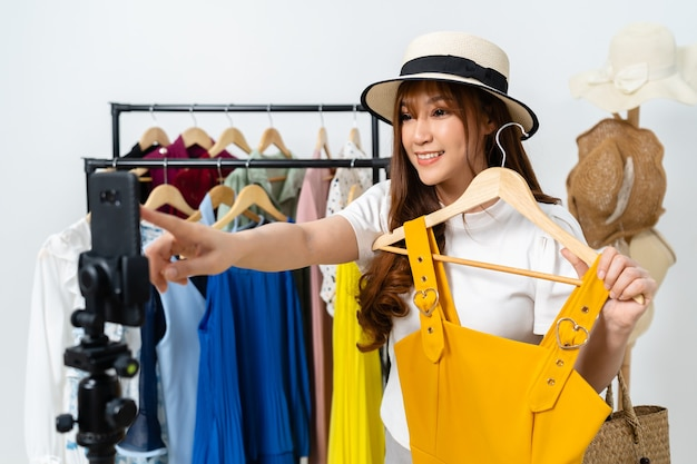 Jovem mulher vendendo roupas e chapéus on-line por streaming ao vivo em smartphone, comércio eletrônico on-line de negócios em casa