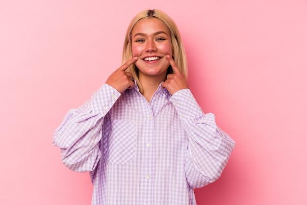 Jovem mulher venezuelana isolada em sorrisos de parede rosa, apontando os dedos para a boca.
