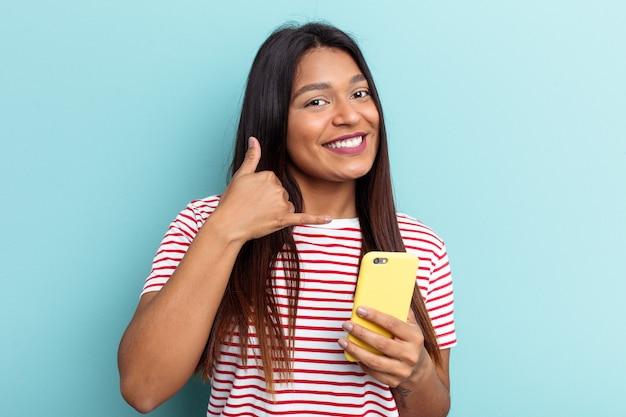 Jovem mulher venezuelana segurando o celular isolado em um fundo azul, mostrando um gesto de chamada de celular com os dedos.