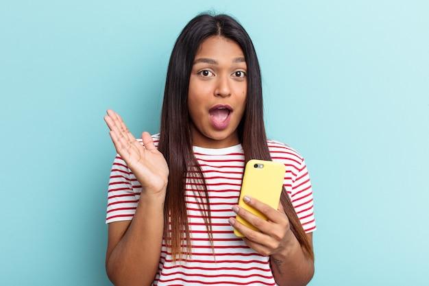 Jovem mulher venezuelana segurando o celular isolado em um fundo azul surpresa e chocada.