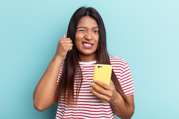 Jovem mulher venezuelana segurando o telefone móvel isolado em um fundo azul, cobrindo as orelhas com as mãos.