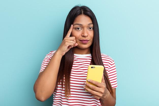 Jovem mulher venezuelana segurando o telefone móvel isolado no fundo azul, apontando o templo com o dedo, pensando, focado em uma tarefa.