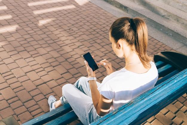 Jovem mulher verifica seu telefone inteligente