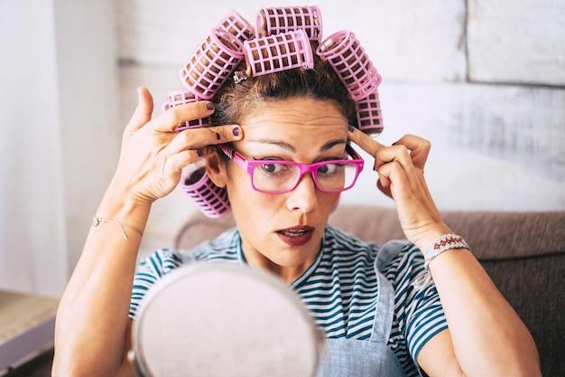 Jovem mulher verificando rugas perto do olho enquanto aplica rolos no cabelo e olhando em frente no espelho, sentado no sofá na sala de estar em casa. mulher bonita em óculos, preparando-se com maquiagem.
