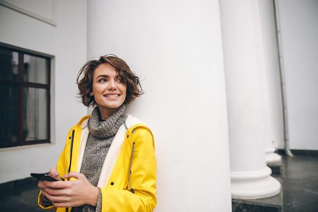 Jovem mulher vestida com capa de chuva caminhando ao ar livre